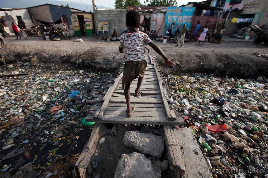 20090825 / Marcelo Min / Fotogarrafa / Epoca / Port-au-Prince / Operação Haiti Missão das Nações Unidas para Estabilização no Haiti (MINUSTAH), Batalhão de infantaria de força de paz Cite Soleil, rio poluído. Crianças atravessam ponte com rio repleto de lixo
