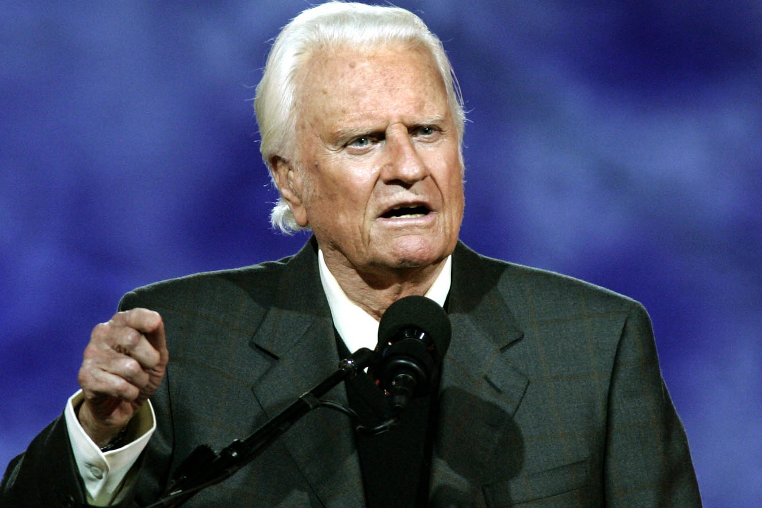 "(FILES)Evangelist Billy Graham delivers his message at the Billy Graham Crusade at Flushing Meadows Park in this June 24, 2005 file photo in Flushing Meadows, New York. US Reverend Billy Graham was hospitalized November 30, 2011 for possible pneumonia, the facility treating the 93-year-old internationally renowned evangelist said. ""He was admitted this afternoon,"" a spokeswoman for Mission Hospital in Asheville, North Carolina told AFP. The hospital said in a statement that he was admitted ""for evaluation and treatment of his lungs,"" and that he was in stable condition and was ""alert, smiling and waving at hospital staff."" AFP PHOTO Timothy A. CLARY (Photo credit should read TIMOTHY A. CLARY/AFP/Getty Images)"